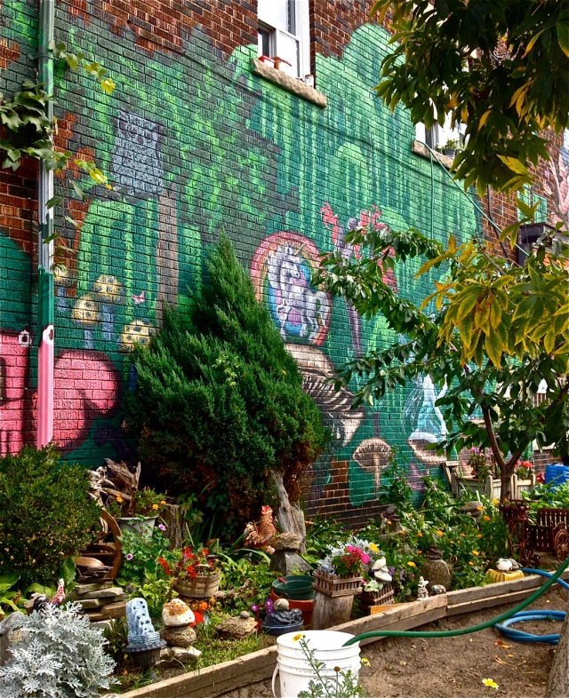 Fairyland Mural painted on a brick wall with willow trees framing a unicorn, fairies, mushrooms, an owl and flowers