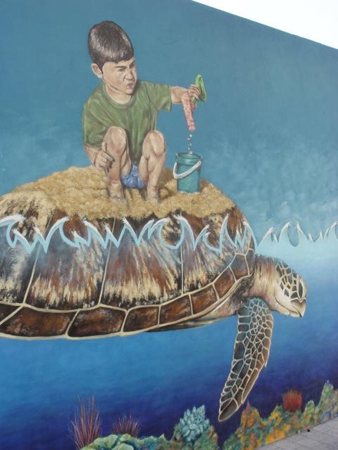 Boy making a sandcastle on turtle-back